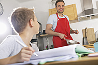 Father preparing food while his son doing his homework - PDF000697