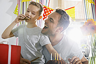 Father and son eating birthday cake - PDF000749