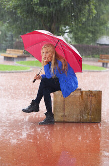 Austria, Thalgau, teenage girl with red umbrella sitting on her suitcase in the rain - WWF003770