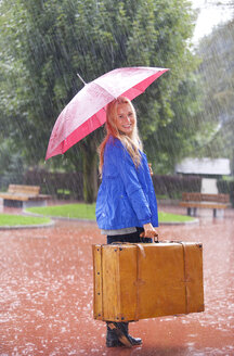Austria, Thalgau, teenage girl with red umbrella standing in the rain with suitcase - WWF003772