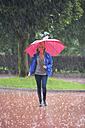 Austria, Thalgau, teenage girl with red umbrella walking in the rain - WWF003774