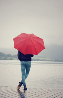 Austria, Mondsee, teenage girl with red umbrella standing at lakeshore - WWF003778