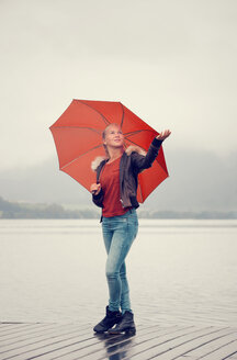 Austria, Mondsee, teenage girl with red umbrella standing at lakeshore - WWF003779