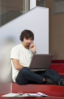 Pensive young man with headphones and laptop - WWF003703