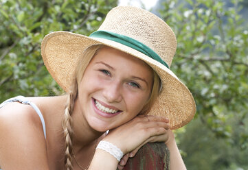 Portrait of smiling teenage girl wearing straw hat - WWF003826