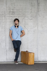 Man with leather suitcase and headphones leaning at concrete wall - WWF003717