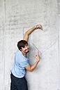 Man embracing graffiti heart on concrete wall - WWF003720