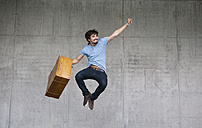 Happy man with leather suitcase jumping in the air - WWF003728