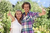 Portrait of smiling young couple showing thumbs up - WWF003853