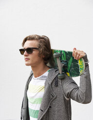 Portrait of young man wearing sunglasses holding skateboard on his shoulders - WWF003846