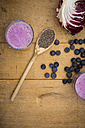 Two glasses of blueberry radicchio smoothie and wooden spoon with chia seeds - LVF002758