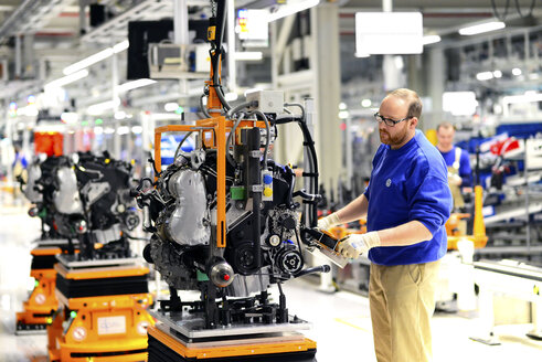Production of VW cars in a factory, worker at gearbox unit - SCH000439