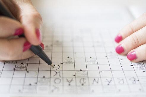 Woman doing crossword puzzle - CHPF000044