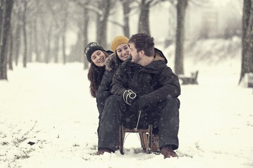 Three friends sitting on sledge in winter - PAF001249