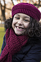 Portrait of smiling little girl with tooth gap wearing wool cap and scarf - MGOF000056
