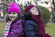 Portrait of two happy little girls back to back in a park on a winter day - MGOF000060