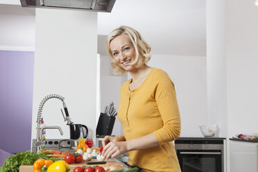 Smiling woman cooking in kitchen - RBF002367