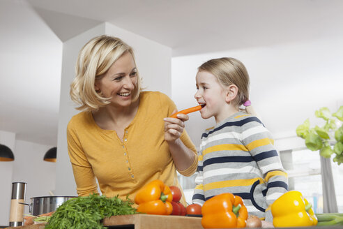 Mother with daughter eating carrot in kitchen - RBF002388