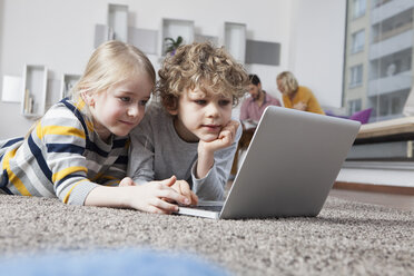 Brother and sister lying on floor using laptop - RBF002406