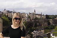 Luxembourg, Luxembourg City, portrait of smiling woman in front of city view - CHPF000037