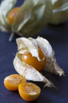 Whole and sliced physalis on slate - YFF000316