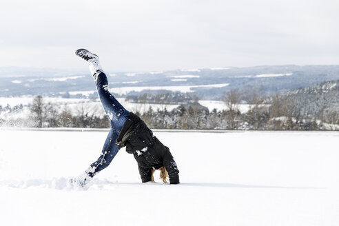 Germany, Baden-Wuerttemberg, Waldshut-Tiengen, playful woman in snow doing a cartwheel - MIDF000052