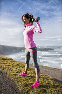 Spain, Gijon, sportive young woman doing workouts at the coast - MGOF000091