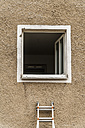 Germany, Munich, ladder leaning at house front with open window - TC004531
