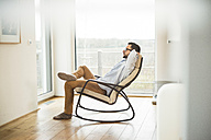 Young man sitting on rocking chair relaxing - UUF003335