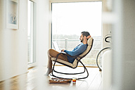 Young man sitting on rocking chair using laptop - UUF003338