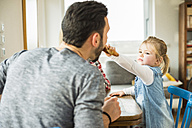 Daughter feeding father at dining table - UUF003373