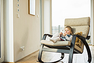 Girl sitting in rocking chair using smartphone - UUF003382