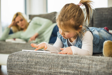 Girl using digital tablet on couch with mother in background - UUF003407