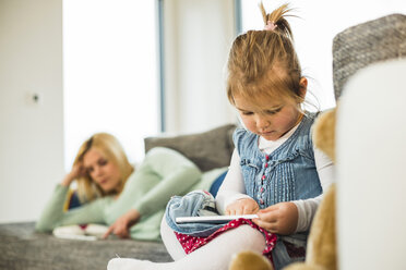 Girl using digital tablet on couch with mother in background - UUF003403
