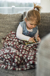 Girl on couch using digital tablet - UUF003409
