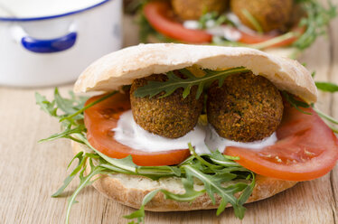 Homemade falafel, tomato, yoghurt sauce, rocket and mint in pita bread on chopping board - ODF001124