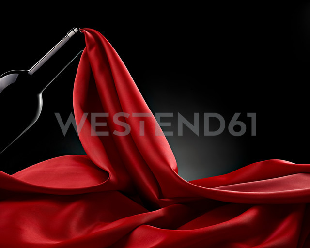 Wine bottle and flowing red silk in front of black background - RAMF000050