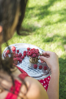 Woman holding metal cup and tray of raspberries - DEGF000134
