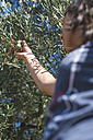 Greece, woman holding twig of olive tree - DEGF000239