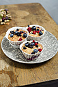 Plate of three cup cakes with berries - MYF000886