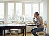 Germany, Cologne, Mature man working from home - RHF000477