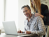 Germany, Cologne, Mature man and adult daughter surfing the web - RHF000482