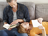 Mature man with adult daughter reading on sofa - RHF000506