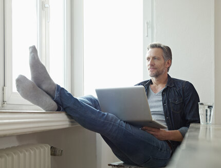 Germany, Cologne, Mature man sitting at window using laptop, feet up - RHF000511