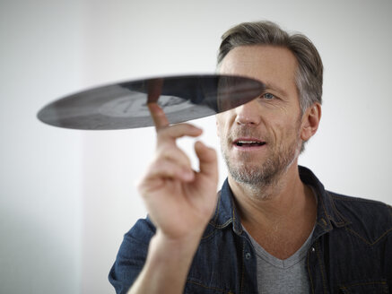 Mature man scrutinizing old vinyl record - RHF000521