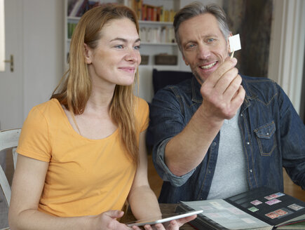 Mature man and young woman looking through stamp collection - RHF000544