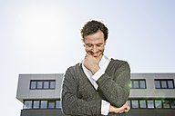 Smiling businessman with hand on chin and closed eyes - PDF000774