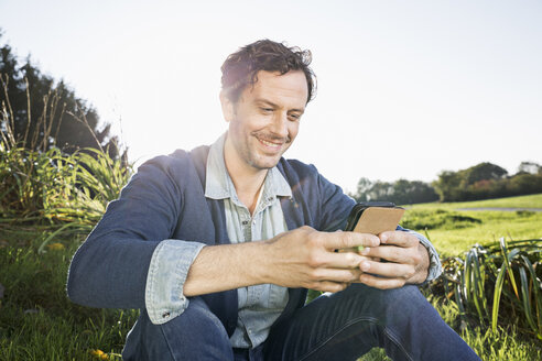 Smiling man sitting on a meadow reading SMS - PDF000802