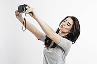 Portrait of young woman taking a selfie with camera - GDF000677
