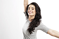 Portrait of happy young woman with outstretched arms - GDF000680